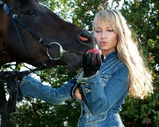 A blonde with a great ass walking with a horse